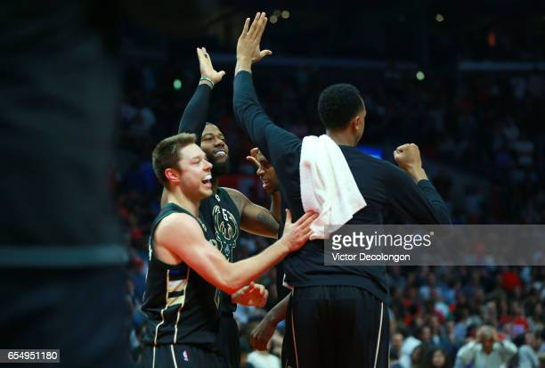 Matthew Dellavedova Greg Monroe and Khris Middleton of the Milwaukee Bucks celebrate with teammate John Henson after defeating the Los Angeles...
