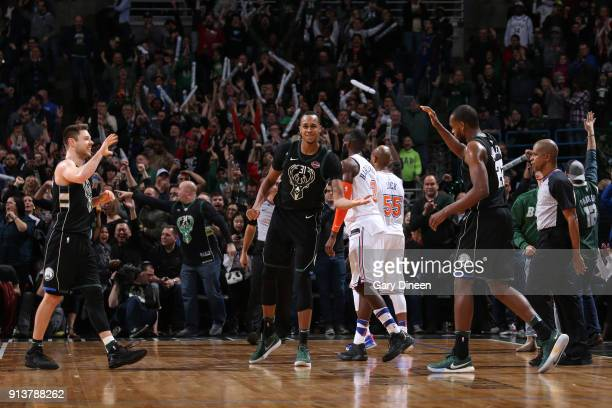 Matthew Dellavedova John Henson and Khris Middleton of the Milwaukee Bucks exchange high fives during the game against the New York Knicks on...