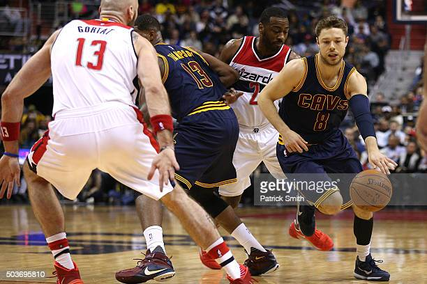 Matthew Dellavedova of the Cleveland Cavaliers dribbles past John Wall of the Washington Wizards during the first half at Verizon Center on January 6...