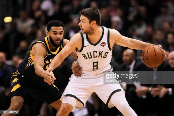 Matthew Dellavedova of the Milwaukee Bucks dribbles the ball while being guarded by Cory Joseph of the Indiana Pacers in the fourth quarter at the...
