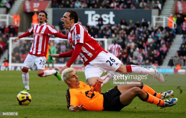 Matthew Etherington of Stoke is brought down by the challenge of Paul Scharner of Wigan during the Barclays Premier League match between Stoke City...