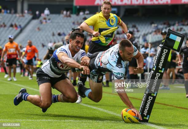 Matthew Evans of the Sharks scores a try in the tackle of Reimis Smith of the Bulldogs during the 2017 Auckland Nines match between the Cronulla...