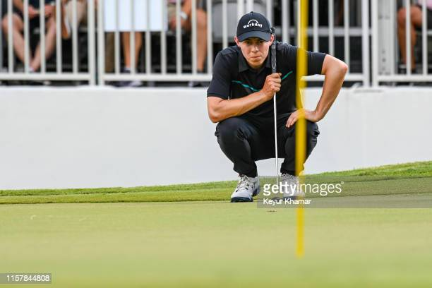 Matthew Fitzpatrick of England reads his putt with the flagstick in on the 17th hole green during the second round of the World Golf...