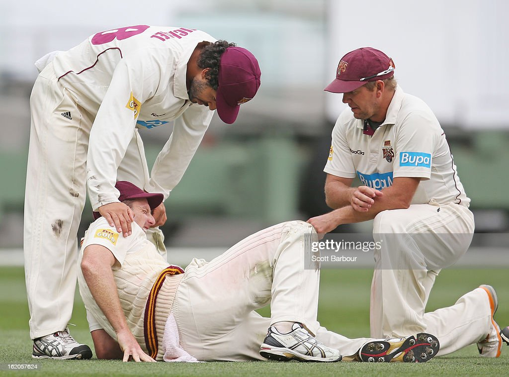 Matthew Gale of the Bulls is comforted by teammates James Hopes and Dominic Michael after injuring his knee while fielding during day two of the Sheffield Shield match between the Victorian Bushrangers and Queensland Bulls at Melbourne Cricket Ground on February 19, 2013 in Melbourne, Australia.