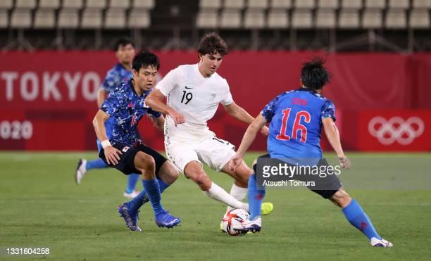 Matthew Garbett of Team New Zealand battles for possession with Wataru Endo of Team Japan during the Men's Quarter Final match between Japan and New...