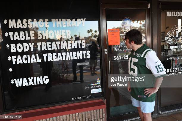 Matthew Gizze, a N.Y. Jet football fan, stops to look at the Orchids of Asia Day Spa where New England Patriots owner Robert Kraft is charged with...