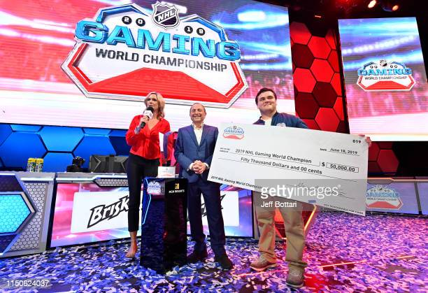 Matthew Gutkoski aka TopShelfCookie poses for a photo with the winner's check as host Kathryn Tappen and NHL Commissioner Gary Bettman look on after...