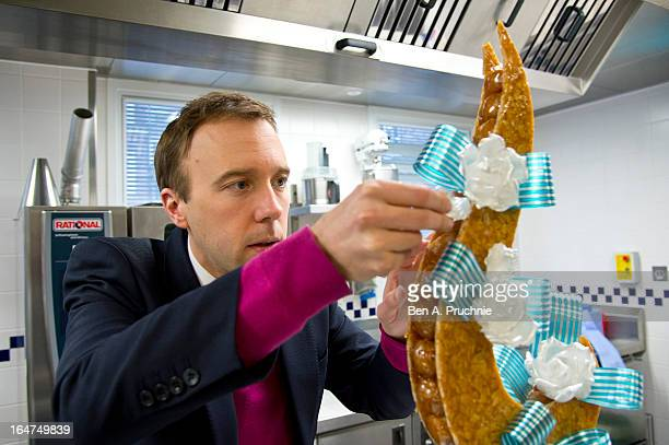 Matthew Hancock MP adds the finishing touches to a croque em bouche during a tour of Le Cordon Bleu's London Centre of Excellence ahead of the...