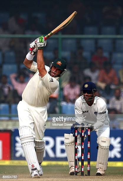 Matthew Hayden of Australia hits a four off the bowling of Amit Mishra watched by wicketkeeper MS Dhoni during day three of the Third Test match...