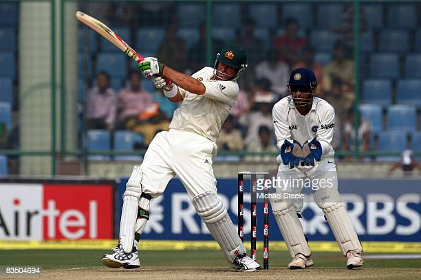 Matthew Hayden of Australia hits a six off the bowling of Amit Mishra watched by wicketkeeper MS Dhoni during day three of the Third Test match...