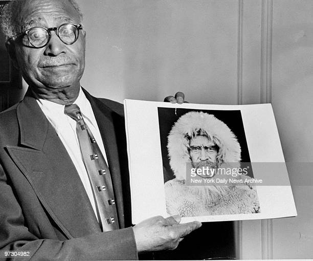 Matthew Henson holds a picture of himself as he appeared when he was a member of Adimiral Perry's expedition to the North Pole