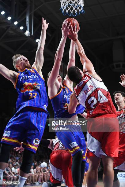 Matthew Hodgson of the Adelaide 36ers forces the ball to the basket defended by Cody Ellis of the Illawarra Hawks knocking Anthony Drmic of the...