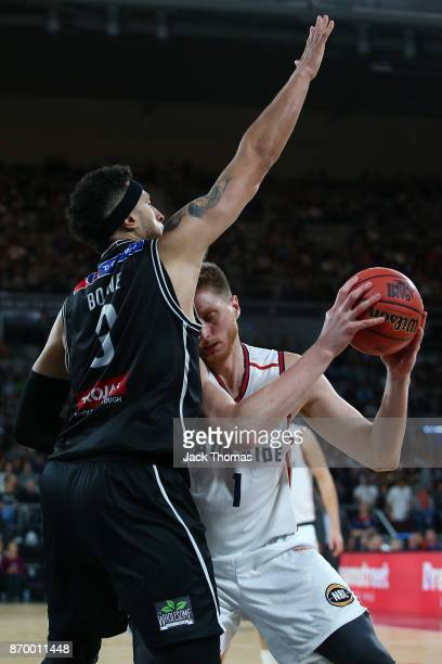 Matthew Hodgson of the Adelaide 36ers is defended by Josh Boone of Melbourne United during the round five NBL match between Melbourne United and the...