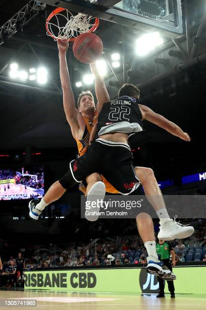 Matthew Hodgson of the Bullets slam dunks as he is challenged by Mason Peatling of United during the NBL Cup match between Melbourne United and the...