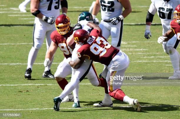 Matthew Ioannidis, and Jonathan Allen of the Washington Football Team tackle Carson Wentz of the Philadelphia Eagles in the second half at FedExField...