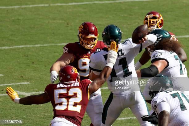 Matthew Ioannidis and Ryan Anderson of the Washington Football Team pressure quarterback Carson Wentz of the Philadelphia Eagles in the second half...