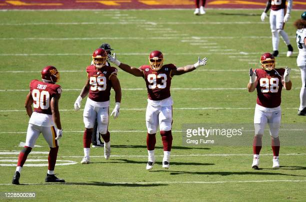 Matthew Ioannidis, Jonathan Allen and Chase Young of the Washington Football Team celebrate a defensive play against the Philadelphia Eagles in the...