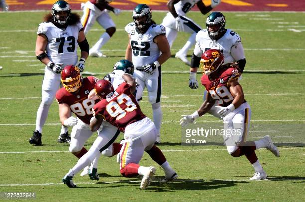 Matthew Ioannidis, Jonathan Allen and Chase Young of the Washington Football Team tackle Carson Wentz of the Philadelphia Eagles in the second half...