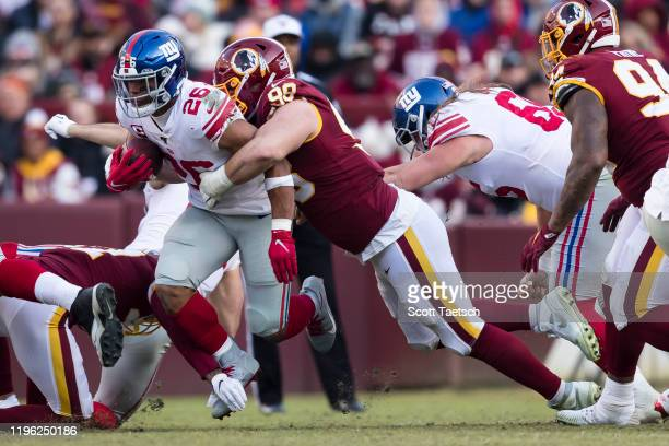 Matthew Ioannidis of the Washington Redskins attempts to tackle Saquon Barkley of the New York Giants during the second half at FedExField on...