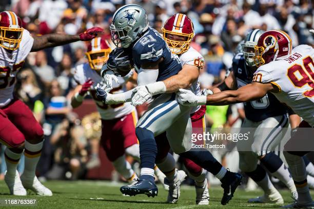 Matthew Ioannidis of the Washington Redskins tackles Ezekiel Elliott of the Dallas Cowboys during the first half at FedExField on September 15 2019...