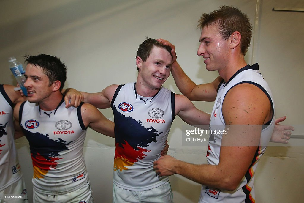 Matthew Jaensch, Patrick Dangerfield and Daniel Talia sing the team song after winning the round two AFL match between the Brisbane Lions and the Adelaide Crows at The Gabba on April 6, 2013 in Brisbane, Australia.