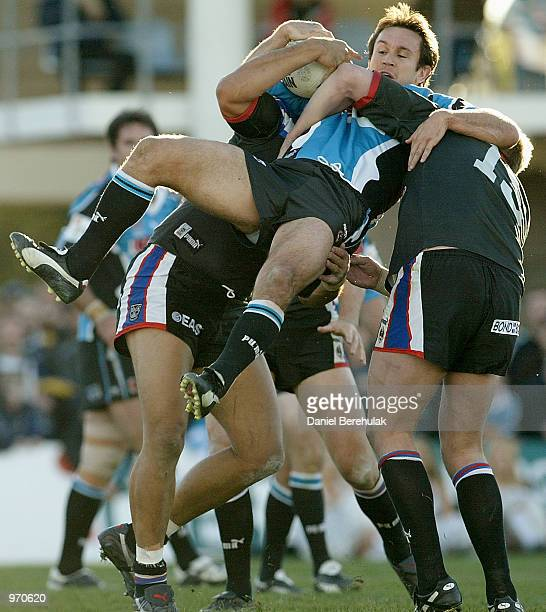 Matthew Johns of the Sharks is tackled by the Warriors defence during the NRL round 17 game between the Sharks and the New Zealand Warriors held at...