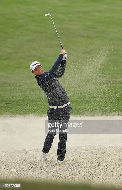 Matthew Jones of Australia plays a bunker shot on the 15th hole during day one of the 2014 Australian Open at The Australian Golf Course on November...