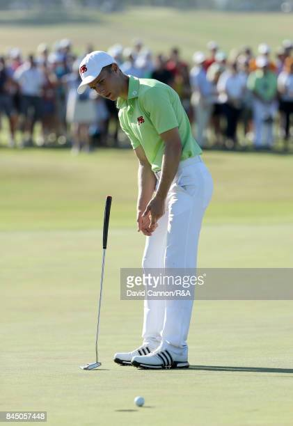 Matthew Jordan of England and the Great Britain and Ireland team lets go his putter as his putt to halve the hole on the 15th hole misses in his...