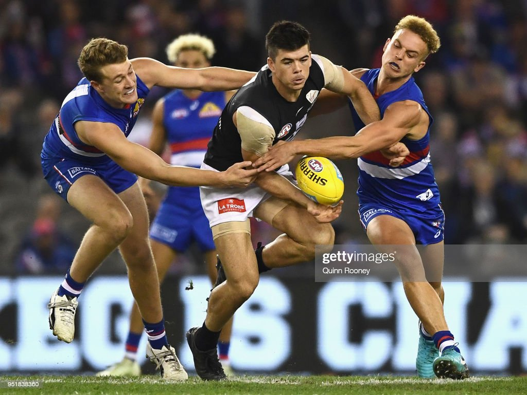 Matthew Kennedy of the Blues handballs whilst being tackled by Jackson Macrae and Mitch Wallis of the Bulldogs during the AFL round six match between the Western Bulldogs and Carlton Blues at Etihad Stadium on April 27, 2018 in Melbourne, Australia.