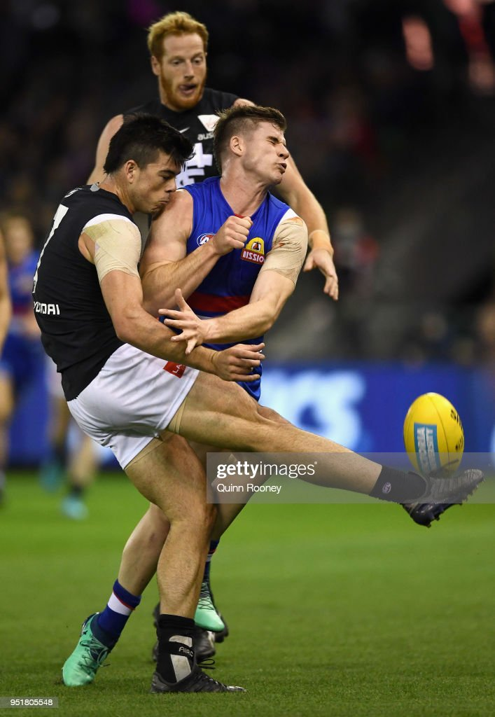 Matthew Kennedy of the Blues kicks whilst being tackled by Billy Gowers of the Bulldogs during the AFL round six match between the Western Bulldogs and Carlton Blues at Etihad Stadium on April 27, 2018 in Melbourne, Australia.