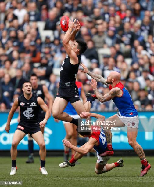 Matthew Kennedy of the Blues marks the ball over Jay Lockhart of the Demons and Nathan Jones of the Demons during the 2019 AFL round 16 match between...