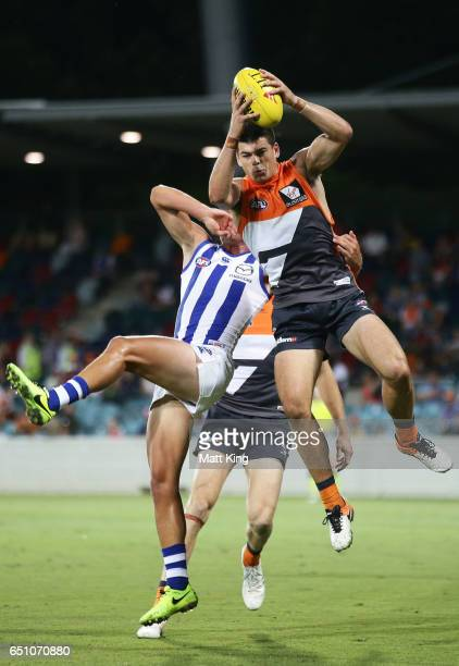 Matthew Kennedy of the Giants takes a mark under pressure from Ryan Clarke of the Kangaroos during the JLT Community Series AFL match between the...