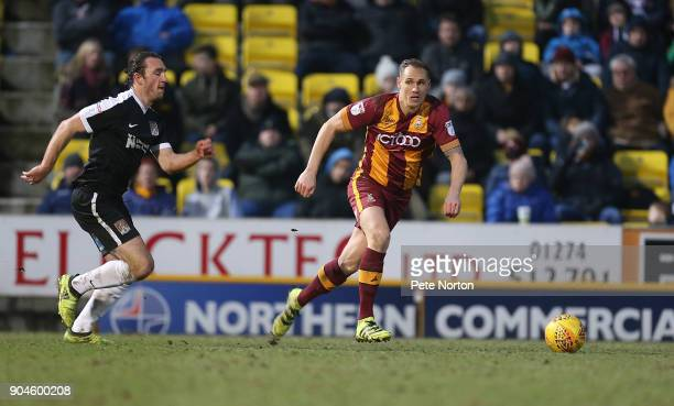 Matthew Kilgallon of Bradford City moves forward with the ball away from JohnJoe O'Toole of Northampton Town during the Sky Bet League One match...
