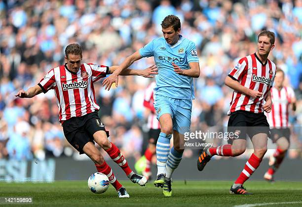 Matthew Kilgallon of Sunderland competes with Edin Dzeko of Manchester City during the Barclays Premier League match between Manchester City and...