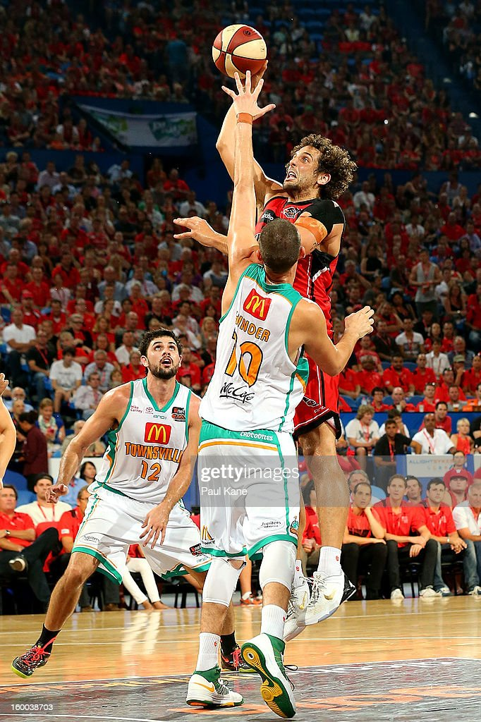 Matthew Knight of the Wildcats takes a jump shot against Russell Hinder of the Crocodiles during the round 16 NBL match between the Perth Wildcats and the Townsville Crocodiles at Perth Arena on January 25, 2013 in Perth, Australia.