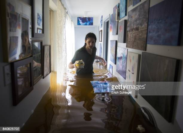 Matthew Koser looks for important papers and heirlooms inside his grandfather's house after it was flooded by heavy rains from Hurricane Harvey...