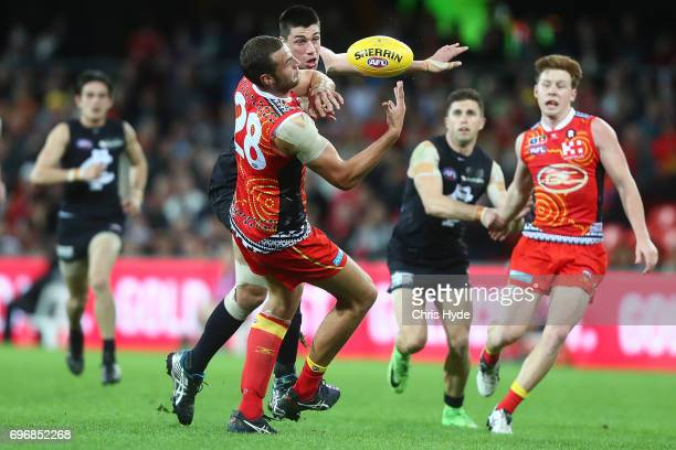 Matthew Kreuzer of the Blues and Jarrod Witts of the Suns compete for the ball during the round 13 AFL match between the Gold Coast Suns and the...