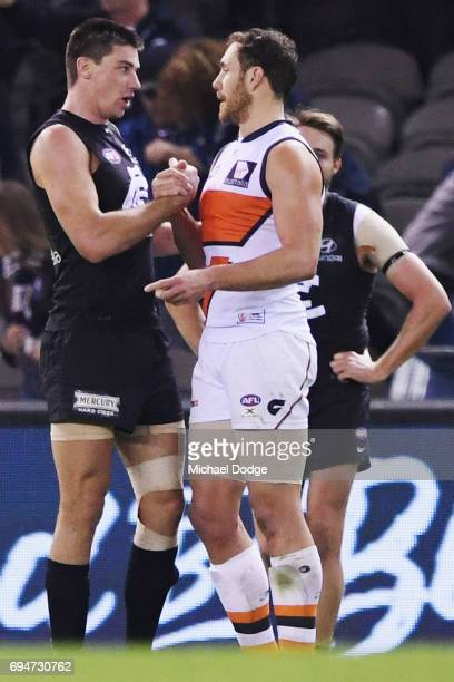 Matthew Kreuzer of the Blues celebrates the win against Shane Mumford of the Giants during the round 12 AFL match between the Carlton Blues and the...