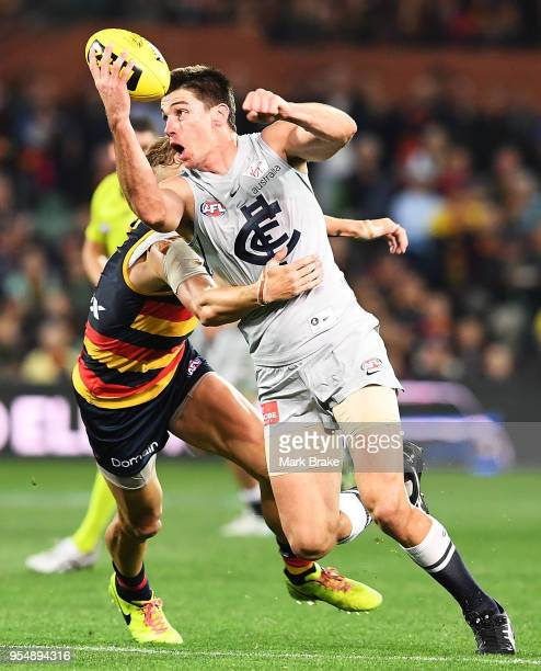 Matthew Kreuzer of the Blues handballs under pressure from Hugh Greenwood of the Adelaide Crows during the round seven AFL match between the Adelaide...