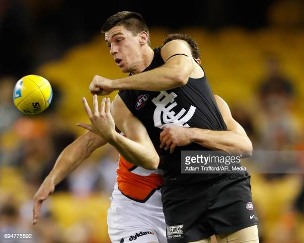 Matthew Kreuzer of the Blues playing his 150th game is tackled by Shane Mumford of the Giants during the 2017 AFL round 12 match between the Carlton...