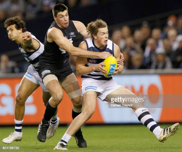 Matthew Kreuzer of the Blues tackles Wylie Buzza of the Cats during the round 19 AFL match between the Carlton Blues and the Geelong Cats at Etihad...