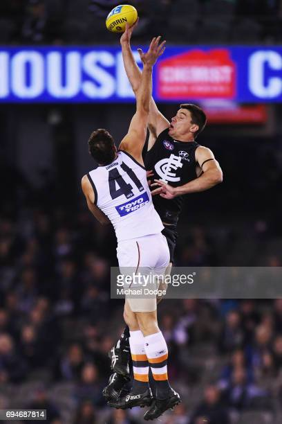 Matthew Kreuzer of the Blues taps the ball away from Shane Mumford of the Giants during the round 12 AFL match between the Carlton Blues and the...