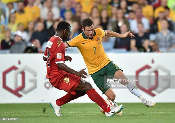 Matthew Leckie of Australia and Abdul Sallam Al Mukhaini of Oman fight for the ball during their Group A football match at the AFC Asian Cup in...