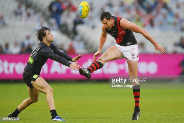 Matthew Leuenberger of the Bombers kicks the ball away from Lachie Plowman of the Blues during the round three AFL match between the Carlton Blues...
