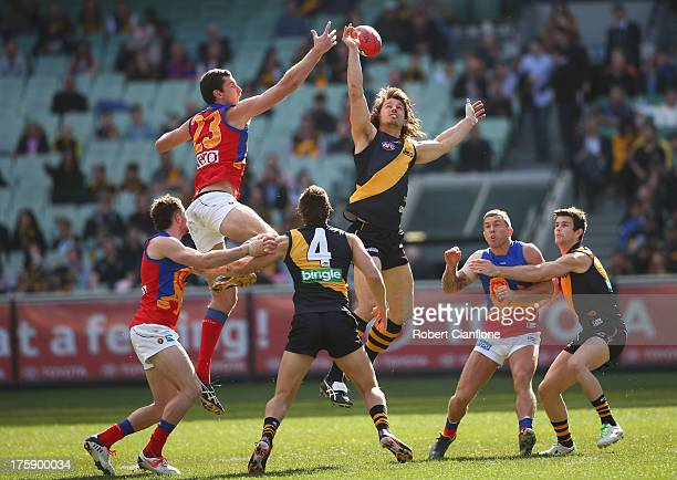 Matthew Leuenberger of the Lions and Ivan Maric of the Tigers challenge eachother for the centre bounce during the round 20 AFL match between the...