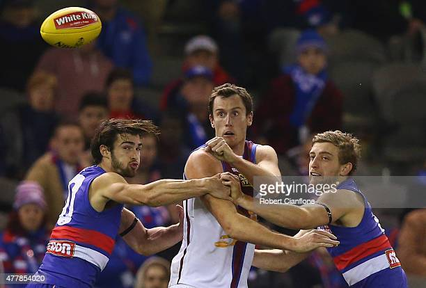 Matthew Leuenberger of the Lions handballs as Easton Wood and Toby McLean of the Bulldogs attempt to tackle during the round 12 AFL match between the...