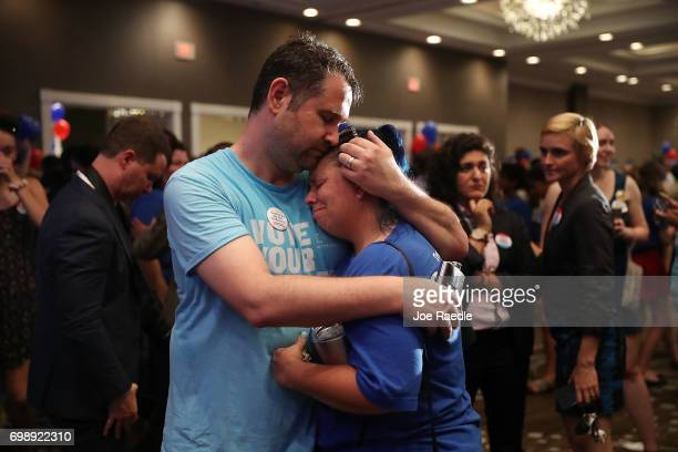 Matthew Levy and Sheila Levy are overcome with emotion after Democratic candidate Jon Ossoff delivers a concession speech during his election night...