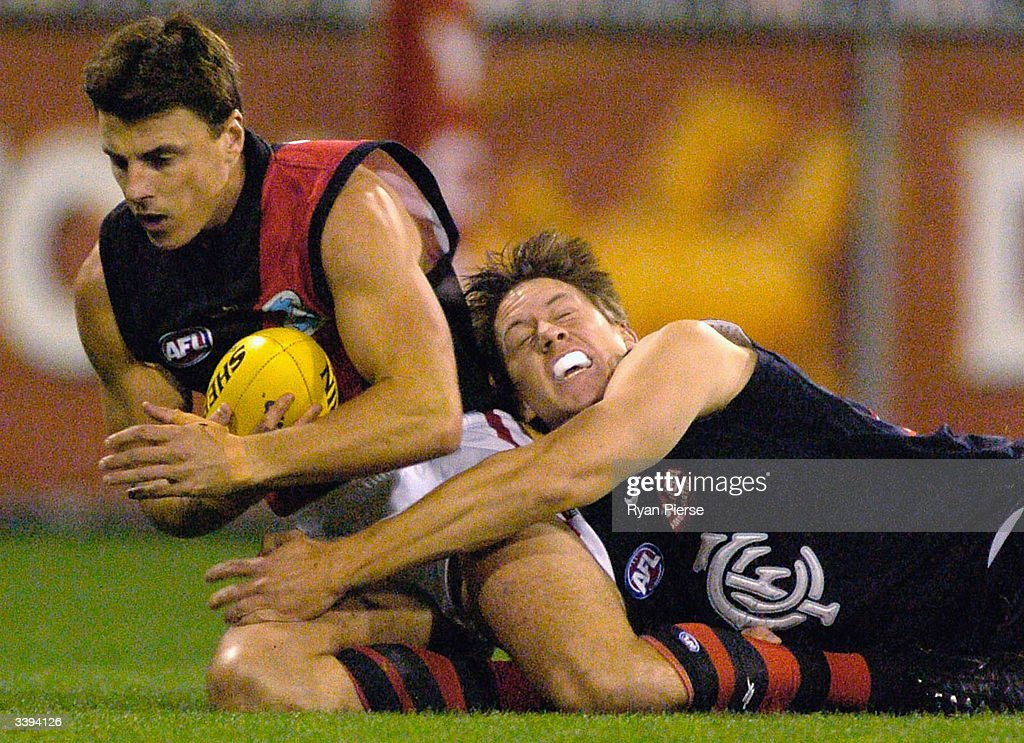 Matthew Lloyd #18 for the Bombers is tackled by Bret Thornton #32 for the Blues during the round four AFL match between The Carlton Blues and the Essendon Bombers at the M.C.G. on April 16, 2004 in Melbourne, Australia.