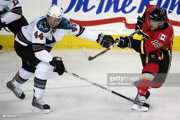 Matthew Lombardi of the Calgary Flames takes a shot from behind defenceman MarcEdouard Vlasic of the San Jose Sharks during game four of the Western...