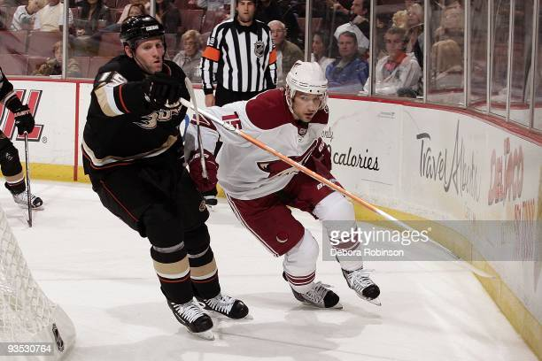 Matthew Lombardi of the Phoenix Coyotes battles for position behind the net against Ryan Whitney of the Anaheim Ducks during the game on November 29...